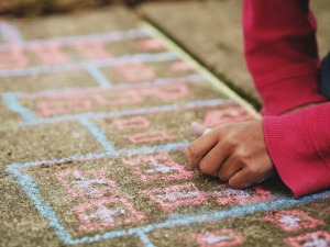 How can I homeschool my child for free? hand using sidewalk chalk on the sidewalk