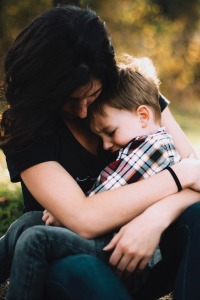 What are the disadvantages of homeschooling? mother holding a crying young boy