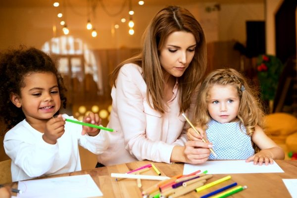 african american child and caucasian child doing worksheets at a table with a caucasian female teacher