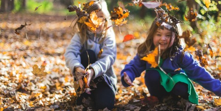 Deschooling Society Summary and Deschooling Society Summary two young girls in woods throwing fall leaves in air