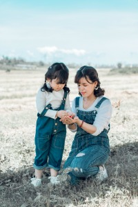 What does it mean to deschool and Is Deschooling for Your Family? mother and daughter looking at something in their hands in a field outside