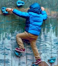 How To Start Deschooling boy in winter coat climbing a rock climbing wall