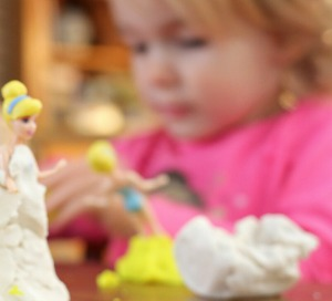 Grace in Christianity Lesson on Grace for Kids little girl playing with playdough on dolls