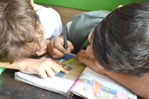 How do homeschoolers teach kindergarten? two little boys completing a workbook