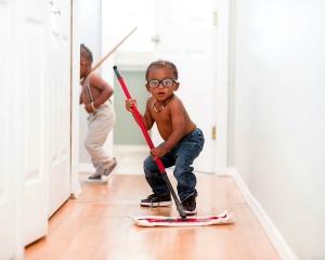 How to Homeschool Kindergarten Tip #7. Practice life skills with your homeschooler. young boy sweeping a hallway in a house