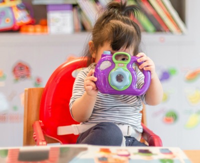 What is Play-Based Learning? preschooler looking through a toy camera with a book open in front of her