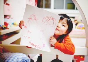 how to homeschool preschool and homeschool kindergarten little girl showing a crayon drawing