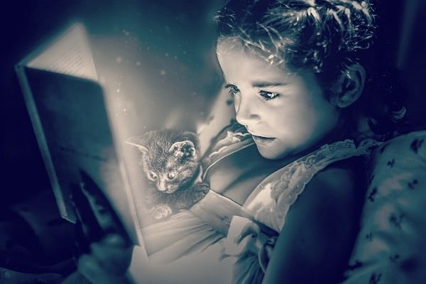 Summer Reading Programs for Free Stuff black and white picture of a little girl reading a book in bed with a kitten sitting on her and looking at the book