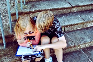 HOW DOES HOMESCHOOLING WORK? a young boy and girl sitting on steps outside looking at school work