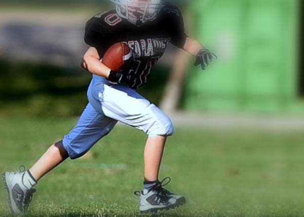 Homeschool Sports Tim Tebow Law child in football uniform running on a field with a football