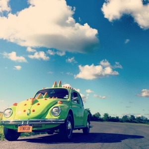 VW bug car decorated like a dinosaur with a blue sky in the background