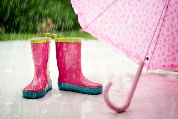 What's the Difference Between Unschooling vs Homeschooling vs Deschooling? pink rain boots and umbrella sitting on a sidewalk in the rain