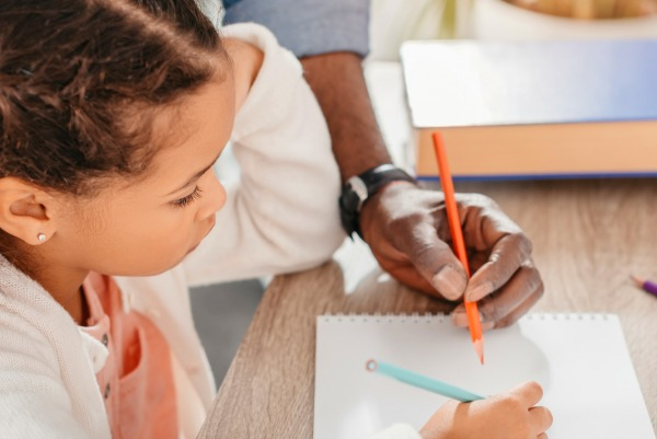 How To Pick Curriculum For Homeschool young african american girl looking down at school work while father helps her