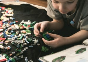 How do I choose a homeschool curriculum? Young boy lying on the carpet playing Lego bricks