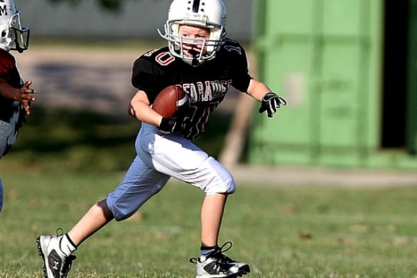 Surprising Answer To Can Homeschoolers Play Sports for Public Schools | Tim Tebow Law boy in a football uniform playing football
