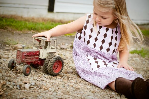 little girl playing with a toy tractor in the dirt
