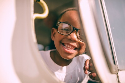 Why Do People Homeschool? smiling boy with glasses looking through a playground tunnel