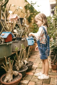 Why Do People Homeschool Reason #6 : Homeschooling focuses on life skills. young girl watering plants on a patio