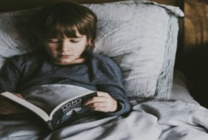 Why do people homeschool? boy reading in bed
