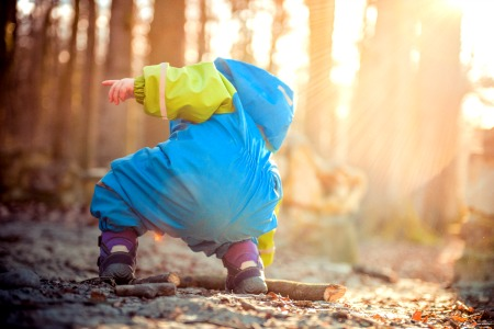 Fun Hiking Supplies To Pack for Kids toddler bending down to pick up something in the woods