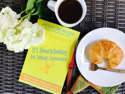 Its Homeschooling Not Solitary Confinement book sitting on a breakfast tray with coffee and a croissant