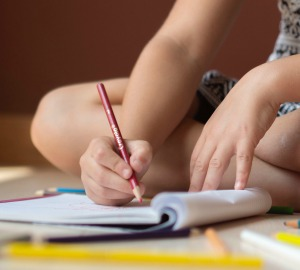 child's hands working on a workbook