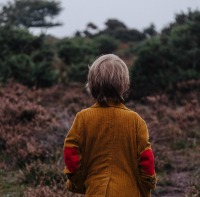 What to pack when hiking with kids boy with his back to the camera looking out at woods