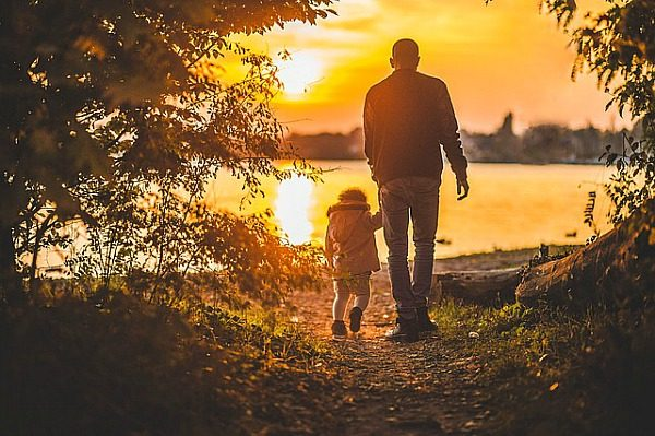 6 Reasons to Visit US National Parks While Traveling With Kids dad holding hand of small child walking toward water with sun setting