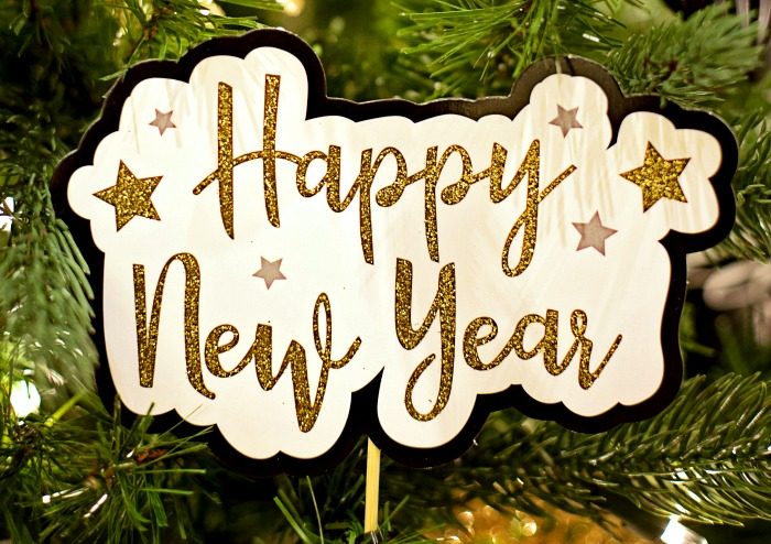 a festive sign with Happy New Year on it with a Christmas tree background