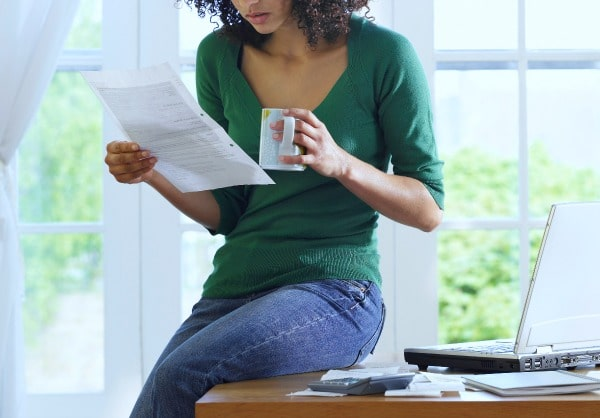 How Do I Get My Homeschool Transcript? African American woman sitting on the edge of a desk at home and looking at a piece of paper while holding a coffee up