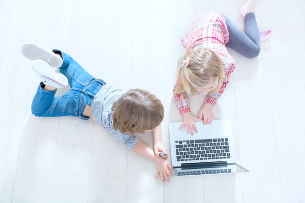 how to start homeschooling TODAY looking down on a little boy and girl lying on their stomachs on a white floor and playing with a laptop
